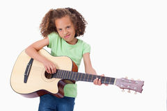 Girl playing the guitar. Against a white background Stock Image