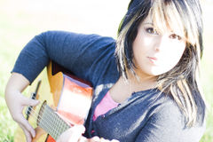 Girl Playing a Guitar Stock Images