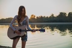 Girl playing guitar on the beach. Sunset Royalty Free Stock Image