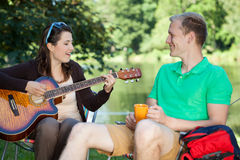 Girl playing guitar on a camping Royalty Free Stock Photography
