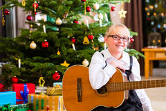 Girl playing guitar on Christmas. Day Royalty Free Stock Photos