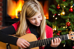 Girl playing guitar on christmas eve Stock Images