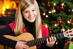 Girl playing guitar on christmas eve Stock Image