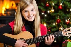 Girl playing guitar on christmas eve Stock Image