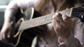 girl playing guitar, closeup hands, mehendi on arm and ring on the finger stock video