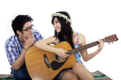 Girl playing guitar with her boyfriend Royalty Free Stock Photography
