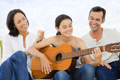 Girl playing guitar with her parents Stock Photo