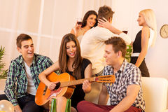 Girl Playing Guitar At House Party Royalty Free Stock Photos