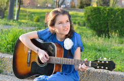 Girl playing guitar in nature Royalty Free Stock Photos