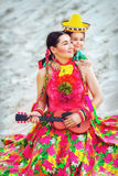 Girl playing the guitar on sand background. Son hugging his mother in Mexican costume and playing the guitar Royalty Free Stock Photography