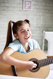 Girl playing guitar at school Royalty Free Stock Image