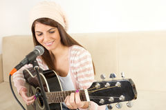 Girl playing guitar and singing on microphone Royalty Free Stock Photos