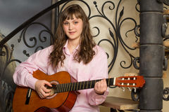 Girl playing the guitar. Teen girl with a guitar sitting on the steps Stock Photos