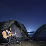 Girl playing guitar at tent glows under a night sky. Stars Stock Photo