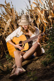 Girl playing guitar in a wheat field Royalty Free Stock Images