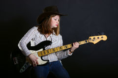 Girl playing gutar. Girl playing guitar on a dark background Royalty Free Stock Photos