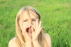 Girl playing on halm of grass Royalty Free Stock Image