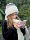 Girl playing hand held game. Cold girl wearing woollen scarf and hat playing hand held game Stock Photography