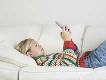Girl Playing Handheld Video Game On Sofa Stock Image