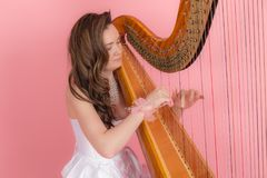 Girl playing the harp Royalty Free Stock Image