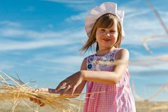 Girl playing with hay during summer day. royalty free stock photo