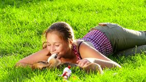 Girl playing with her beagle dog in park. Slow. Girl playing with her beagle dog in park. Girl playing with her beagle dog in summer park. beautiful girl near a stock footage