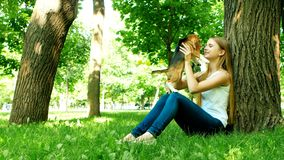 Girl playing with her beagle dog in summer park. Beautiful girl near a tree, kissing the dog's nose stock video footage