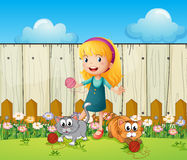 A girl playing with her cats inside the fence Stock Images