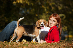 Girl playing with her  dog in autumn park Royalty Free Stock Images