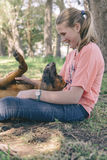 Girl playing with her dog outdoors Stock Images