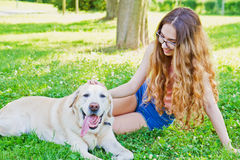 A Girl playing with her labrador retriever dog in the park Stock Images