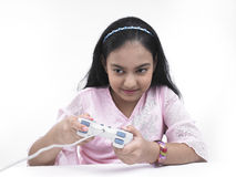 Girl playing on her playstation. Asian teenage girl of indian origin playing with her play station Royalty Free Stock Photos
