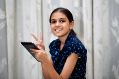 Girl playing with her tab. Ten year girl playing with her tablet pc or tab in her house sitting on a sofa or a wooden chair against white curtain and showing a Stock Image