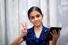 Girl playing with her tab. Ten year girl playing with her tablet pc or tab in her house sitting on a sofa or a wooden chair against white curtain and showing a Stock Photography