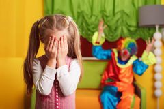 Girl playing hide and seek with a cheerful clown. Stock Image