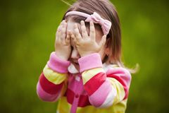 Girl is playing hide-and-seek hiding face Stock Photography
