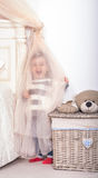 Girl playing hide and seek. Little girl hiding behind a curtain in the bedroom Royalty Free Stock Photo