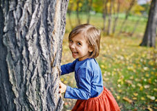 Girl Playing Hide and Seek in Park Royalty Free Stock Image