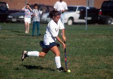 A girl playing high school field hockey game royalty free stock photo