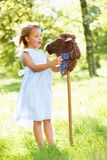 Girl Playing With Hobby Horse In Summer Field Stock Photo