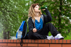 Girl playing hookey and drinking alcohol Stock Image