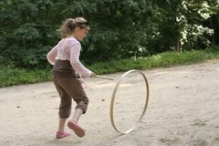 Girl playing a hoop racing game Stock Photos