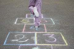 Girl Playing Hop-Scotch In Playground Stock Photography