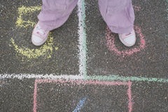 Girl Playing Hop-Scotch In Playground Stock Image