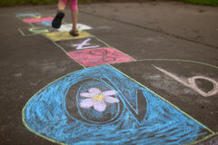 A girl playing hopscotch. A girl playing colorful hopscotch in pink leggins Stock Image