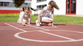 Girl playing Hopscotch. Little cute girls draws Hopscotch on asphalt by chalk. Children playing on playground outdoors. Kids jumps hopscotch at park stock footage