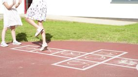 Girl playing hopscotch. Tracking shot of a girl jumping while playing Hopscotch at park. Little cute girls on children playground outdoors. Legs of kids jumps stock footage