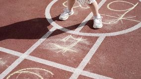 Girl playing hopscotch. Tracking shot of a girl jumping while playing Hopscotch at park. Little cute girls on children playground outdoors. Legs of kids jumps stock video