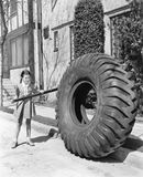 Girl playing with a huge tire and stick Stock Photos