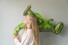 A girl playing with inflatable dinosaur stock photography